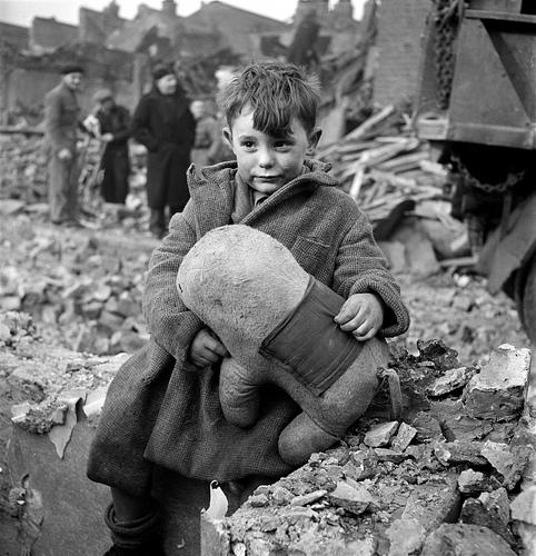 Момче, което държи играчка в опустошения Лондон, 1945 г.